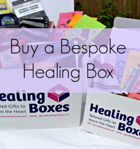 Text ' Buy a Bespoke Healing Box' on a purple banner over image of two healing boxes hospital wellness gifts
