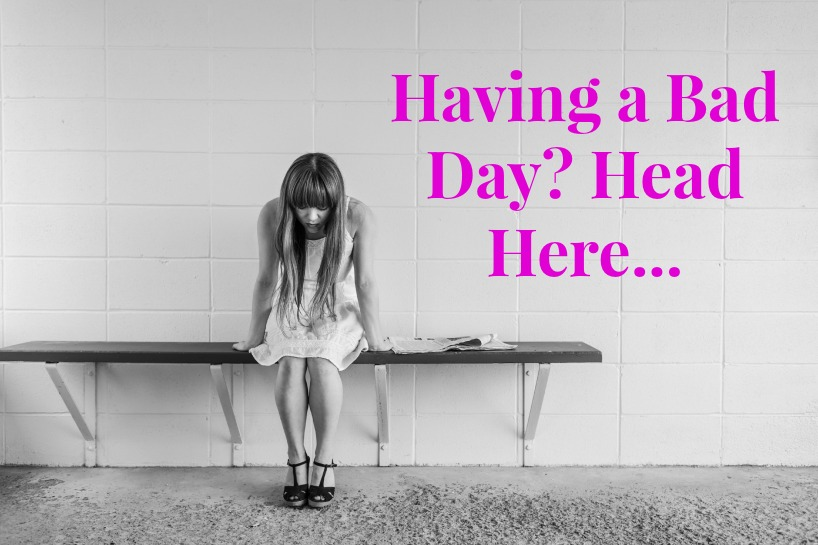 black and white photo woman with head lowered pink text: having a bad day? Head here...