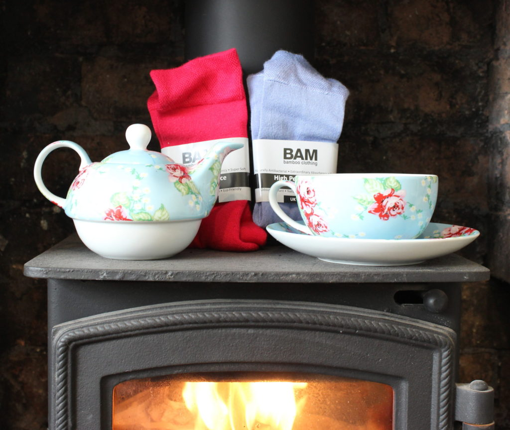 a lit wood burner in a old brick fireplace, on top are 2 pairs of bamboo socks, pink and blue and a rose patterned tea pot, tea cup and saucer