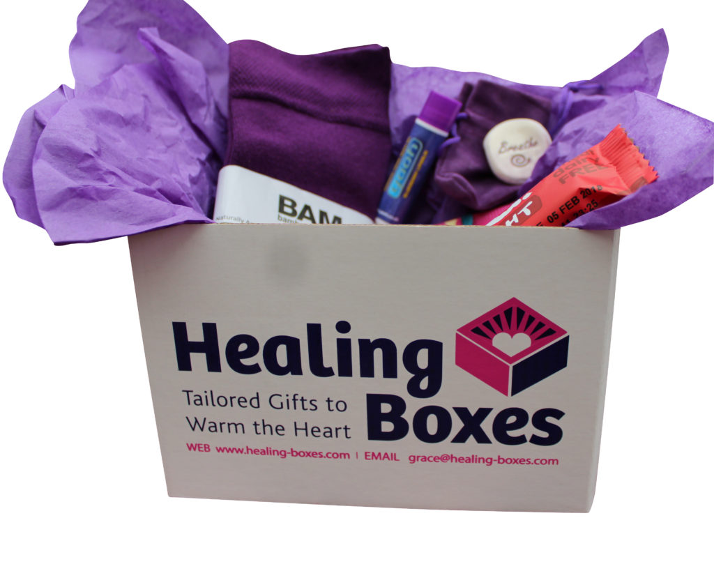 A photograph of a healing box containing purple tissue paper, socks, lip balm, a palm stone and a health food bar