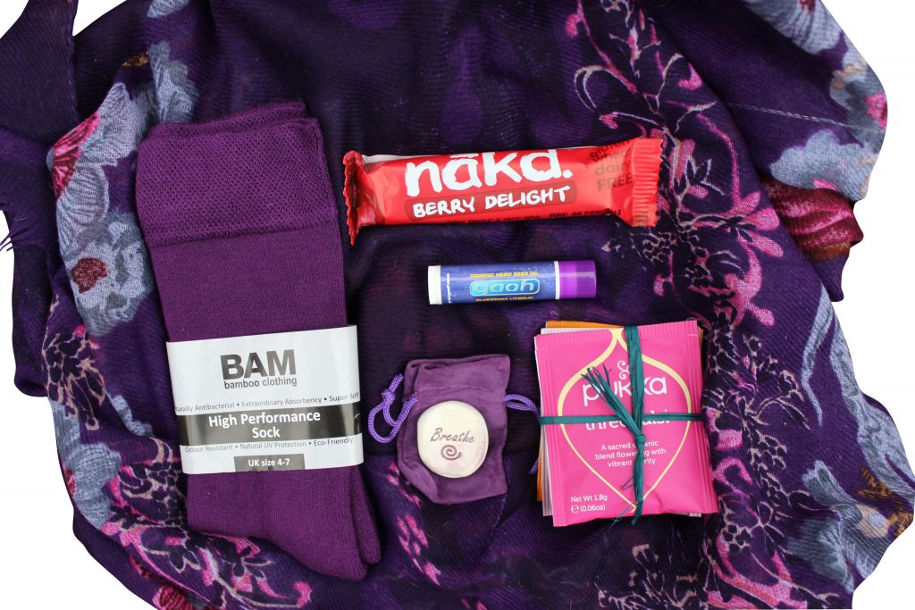 contents of a self care subscription box on a purple cloth shot taken from above. Contains socks, palm stone, tea bags, lip balm and snack ba