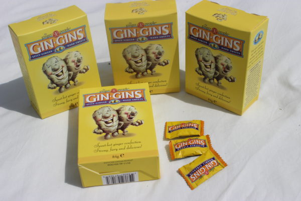 Four boxes of ginger sweets, with some loose sweets scattered about.