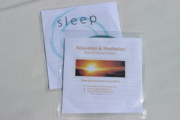 Two meditation CDs laid on top of each other on white background