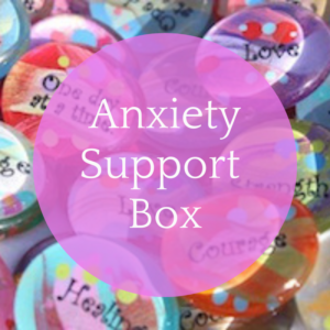 Anxiety support box: text on pink bubble over photograph of pile of colourful glass palm stones with empowering words on them